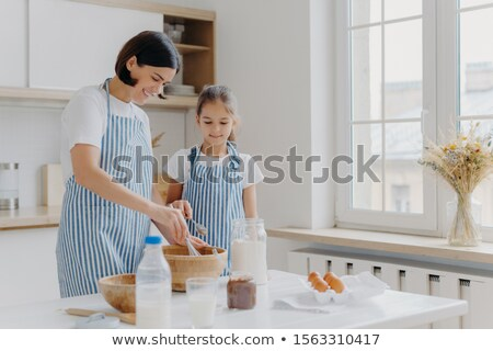 Horizontal shot of caring mother and daughter cook together, mom gives culinary lesson to small girl Stock photo © vkstudio
