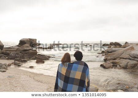 Rear view of young Caucasian couple wrapped in blanket standing at beach. They are looking the sea Stock photo © wavebreak_media