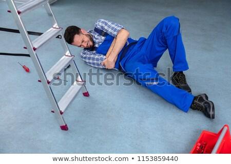 мастер на все руки лестница бессознательный шлема полу работу Сток-фото © AndreyPopov
