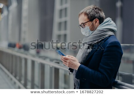 Sideways shot of male blogger sends text messages and reads comm Stock photo © vkstudio