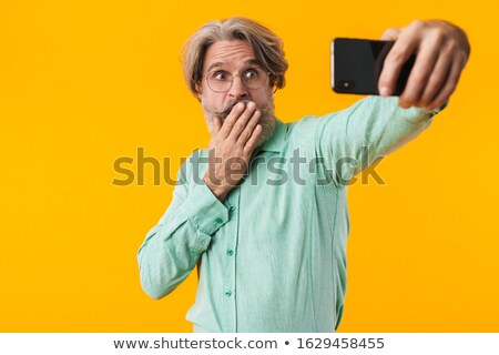 Shocked grey-haired man take a selfie by mobile phone. Stock photo © deandrobot