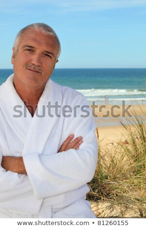 Middle aged man in a toweling robe by the sea stock photo © photography33