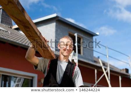 carpenter carrying planks of wood over shoulder stock photo © photography33