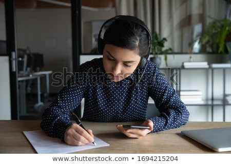 businesswoman with cellphone and writing in organizer stock photo © vlad_star