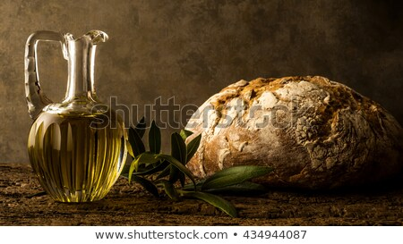 Virgin olive oil in vintage oil jar and rustic bread Stock photo © marimorena