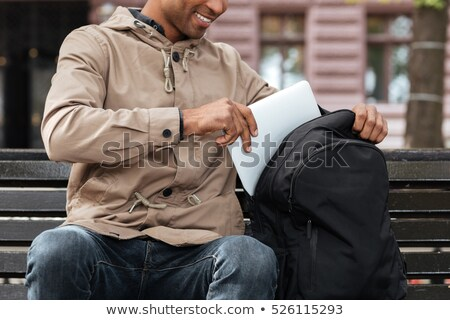 cropped photo of african man getting laptop from backpack stock photo © deandrobot