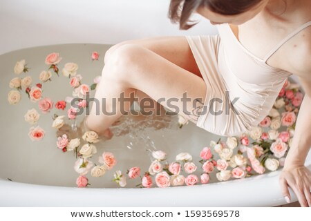 Stock photo: woman in a bath with flower petals