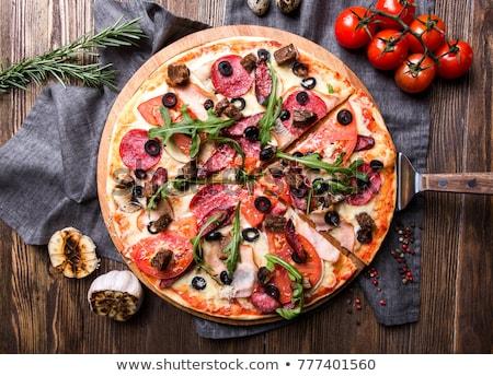 tasty italian pizza served on a dark wooden table stock photo © yatsenko