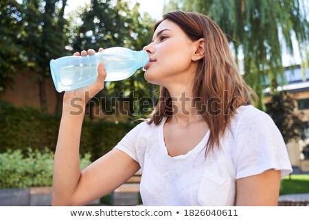Geconcentreerde fitness dame vergadering buitenshuis drinkwater Stockfoto © deandrobot
