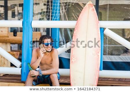 Férfi ül szörfdeszka ivóvíz mosolyog tengerpart Stock fotó © IS2