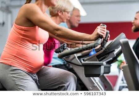 mulher · grávida · ciclismo · fitness · sorridente · exercer · máquina - foto stock © vilevi