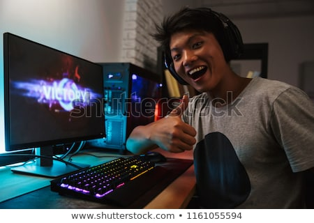 Happy asian gamer guy 16-18 rejoicing victory while playing vide Stock photo © deandrobot
