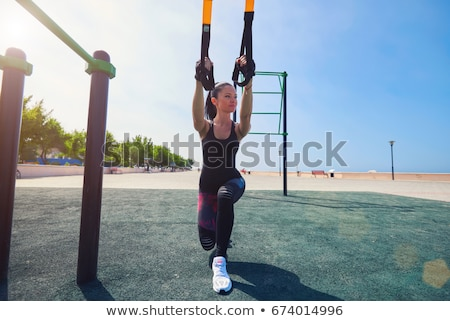 Women doing push ups training arms with trx fitness straps in th Stock photo © boggy