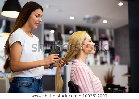 Hairstylist combing the client's hair Stock photo © Kzenon