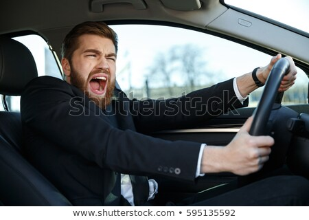Portrait of a screaming businessman nearly crashing car Stock photo © deandrobot