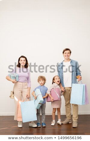 Happy young parents with paperbags and two little kids with giftboxes Stock photo © pressmaster
