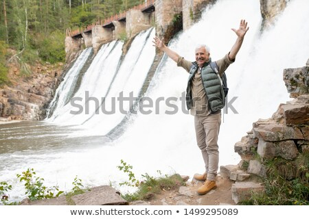 Mature ecstatic male hiker with raised arms standing on rock by waterfalls Stock photo © pressmaster