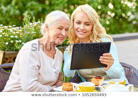 daughter with tablet pc and senior mother at cafe stock photo © dolgachov