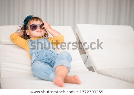 A little girl in fashionable glasses on the terrace background with long curly hair smiles in front  Stock photo © ElenaBatkova