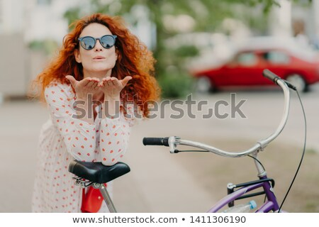 Affectionate redhead woman sends air kiss to lover on street, keeps palms near mouth, wears round sh Stock photo © vkstudio