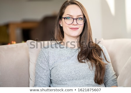 Image of young woman in eyeglasses smiling while resting on sofa Stock photo © deandrobot