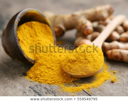 Turmeric powder in a wooden spoon on a yellow background Stock photo © galitskaya