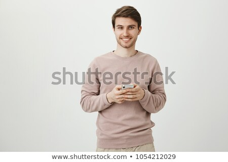 Image of young bearded man holding smartphone isolated over whit Stock photo © deandrobot