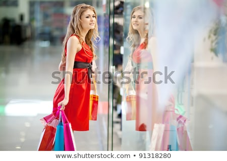 photo of young joyful woman with shopping bags inside mall stock photo © hasloo