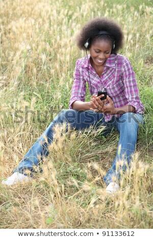 afroamerikai · nő · ülő · magas · fű · hallgat · kedvenc - stock fotó © photography33