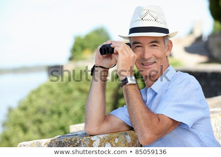 senior gentleman admiring view with binoculars Stock photo © photography33