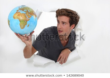 Man popping out a ripped wall in paper holding a globe. Stock photo © photography33