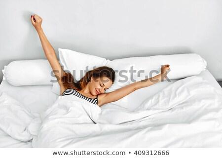 mosolygó · nő · felfelé · párna · fehér · női · mosolyog - stock fotó © wavebreak_media