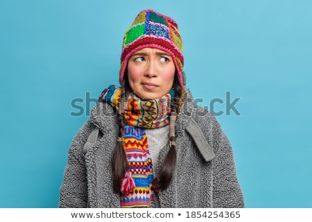 Pensive attractive young woman in knitted dress standing and stretching Stock photo © deandrobot