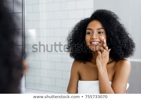 Smiling woman with cream applied to face Stock photo © LightFieldStudios