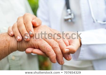 close up of doctor holding old man hand stock photo © dolgachov