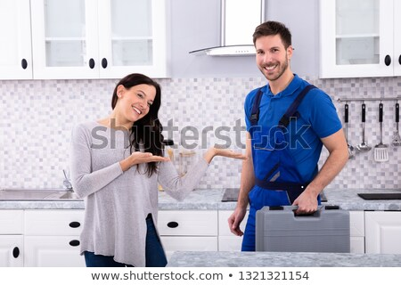 woman presenting male repairman in kitchen stock photo © andreypopov