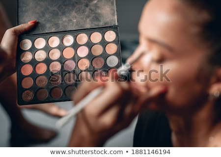Make-up artist doing bright make up of stylish brunette girl with long hair, making face with closed Stock photo © studiolucky
