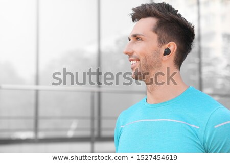 Smiling young sportsman in wireless earphones Stock photo © deandrobot