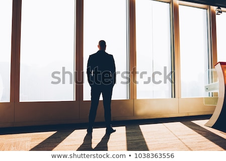 modern man thinking while standing with hand in pocket Stock photo © feedough