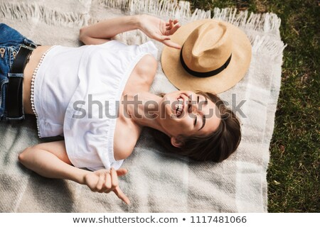 Top view of a happy young girl in summer hat laying Stock photo © deandrobot