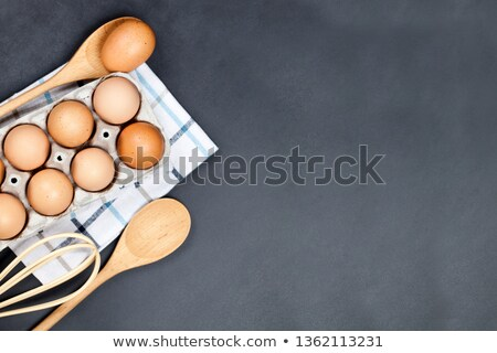 fresh eggs and kitchen utensil on backboard background stock photo © marylooo