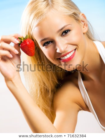 happy woman eating strawberries on summer beach stock photo © dolgachov
