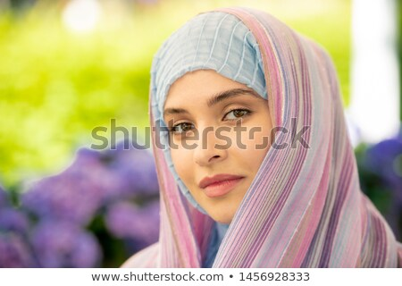 Young serene female in traditional hijab looking at you Stock photo © pressmaster