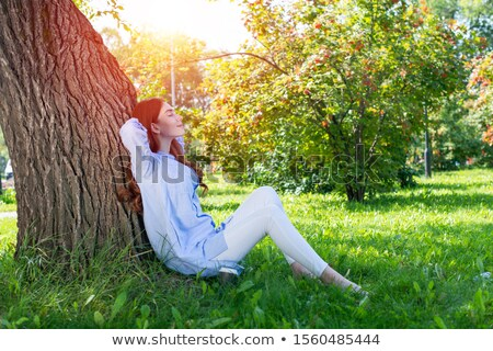 portrait of redhead young woman leaning on tree stock photo © diego_cervo