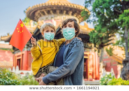 Enjoying vacation in China. Happy family in medical mask with national chinese flag in Forbidden Cit Stock photo © galitskaya