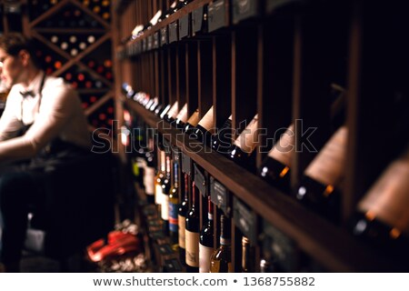 Portrait of confident male with a selection of wines in the back Stock photo © HASLOO