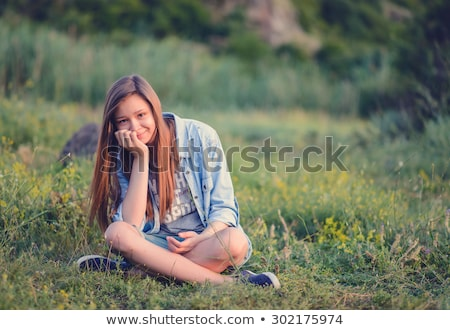 Pretty Smiling Woman Sitting on Grassy Ground Stock photo © dash