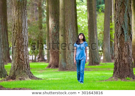 Young teen biracial girl walking under tall trees Stock photo © jarenwicklund