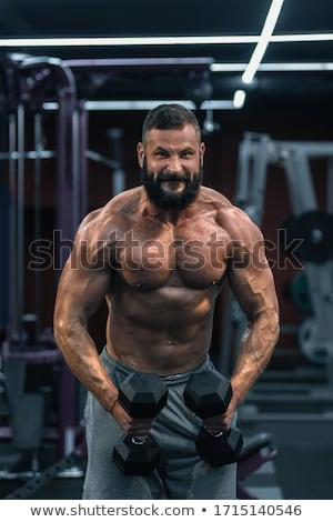 Portrait of muscular man lifting dumbbells Stock photo © wavebreak_media
