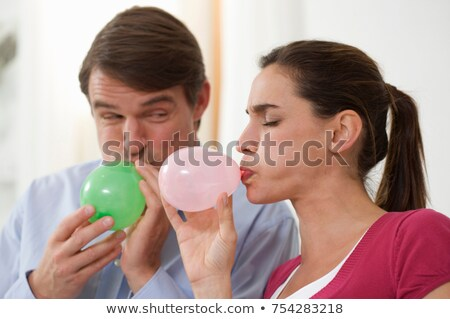 Stock photo: a couple trying to blow balloons